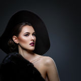 Beautiful girl in fur coat and hat. Beautiful young woman with glamorous make-up in luxurious fur coat on naked body and fashion hat on black background. Copy Royalty Free Stock Image