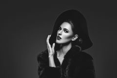 Beautiful girl in fur coat and hat. Beautiful young woman with glamorous make-up in luxurious fur coat on naked body and fashion hat on black background. Copy Stock Images