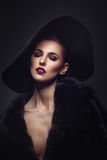 Beautiful girl in fur coat and hat. Beautiful young woman with glamorous make-up in luxurious fur coat on naked body and fashion hat on black background. Copy Royalty Free Stock Photos