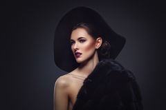Beautiful girl in fur coat and hat. Beautiful young woman with glamorous make-up in luxurious fur coat on naked body and fashion hat on black background. Copy Stock Photography