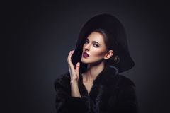 Beautiful girl in fur coat and hat. Beautiful young woman with glamorous make-up in luxurious fur coat on naked body and fashion hat on black background. Copy Royalty Free Stock Images