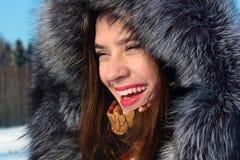 Beautiful girl in fur coat with hood laughs outdoor Stock Photos