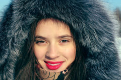 Beautiful girl in fur coat with hood smiles Royalty Free Stock Image