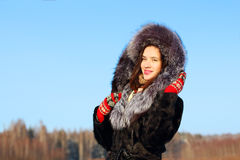 Beautiful girl in fur coat with hood smiles outdoor Royalty Free Stock Photos
