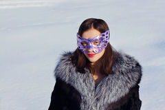 Beautiful girl in fur coat and mask Royalty Free Stock Image