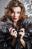 Beautiful girl in fur coat. Beautiful girl with red lips in black-white silver fox fur coat Royalty Free Stock Photos