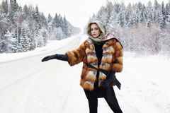 Beautiful girl in a fur coat waiting for the car on a winter road in the forest Royalty Free Stock Images