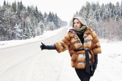 Beautiful girl in a fur coat waiting for the car on a winter road in the forest Stock Photo