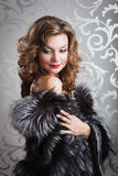 Beautiful girl in fur coat. Young beautiful woman with make up in black-white fur coat Stock Photography