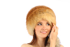 Beautiful girl in fur hat over white. Close up portrait of young beautiful girl in fur hat over white background royalty free stock photography