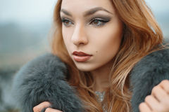 Beautiful girl in a fur jacket Stock Images