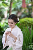 Beautiful girl is in garden and drinking tea Royalty Free Stock Photos