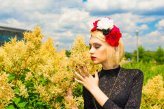 Beautiful girl with garland of wild flowers on her head. Smelling flower Royalty Free Stock Photos
