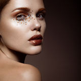 Beautiful girl with a gentle make-up and crystals on the face. Stock Image