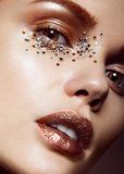 Beautiful girl with a gentle make-up and crystals on the face. Close-up portrait. Stock Photo