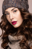 Beautiful girl with gentle makeup, curls in brown knit hat. Warm winter image. Beauty face. Royalty Free Stock Photo