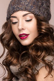 Beautiful girl with gentle makeup, curls in brown knit hat. Warm winter image. Beauty face. Stock Photos