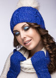 Beautiful girl with gentle makeup, curls and smile. Beautiful girl with a gentle make-up, curls and a smile in winter blue knit cap. Warm winter image. Beauty stock image