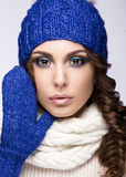 Beautiful girl with gentle makeup, curls and smile. Beautiful girl with a gentle make-up, curls and a smile in winter blue knit cap. Warm winter image. Beauty stock photo