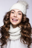 Beautiful girl with gentle makeup, curls and smile in white knit hat. Warm winter image. Beauty face. Royalty Free Stock Photography