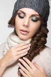 Beautiful girl with gentle makeup, design manicure. Beautiful girl with a gentle make-up, design manicure and winter gray knit cap. Warm winter image. Beauty royalty free stock image