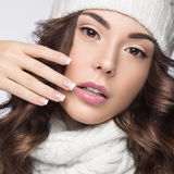 Beautiful girl with gentle makeup, design manicure and smile in white knit hat. Warm winter image. Beauty face. Stock Photo