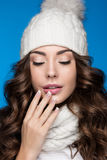 Beautiful girl with gentle makeup, design manicure and smile in white knit hat. Warm winter image. Beauty face. Stock Photos