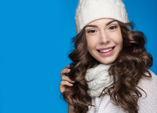 Beautiful girl with gentle makeup, design manicure and smile in white knit hat. Warm winter image. Beauty face. Royalty Free Stock Image