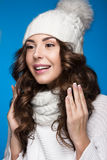Beautiful girl with gentle makeup, design manicure and smile in white knit hat. Warm winter image. Beauty face. Royalty Free Stock Photography