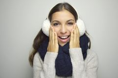 Beautiful girl with gentle makeup, wavy hair and smile with earmuffs, scraf and sweater. Warm winter image. Beauty face Royalty Free Stock Image