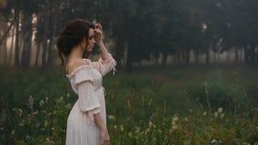 Beautiful girl in white dress posing on camera.