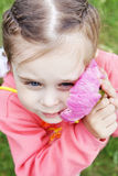Beautiful girl gently presses to cheek a big pink flower Royalty Free Stock Photography