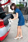 Beautiful girl gets out his suitcase out of the ca Royalty Free Stock Images