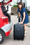 Beautiful girl gets out his suitcase out of the ca Royalty Free Stock Image