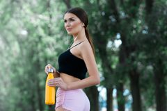 Beautiful girl getting ready for jogging in the park. With thermos bottle in hand. royalty free stock images