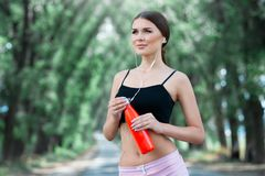 Beautiful girl getting ready for jogging in the park. With thermos bottle in hand. stock photos