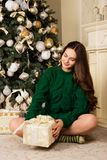 Beautiful girl with a gift in hand, sitting on the carpet near the Christmas tree.  Royalty Free Stock Photos