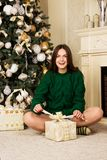 Beautiful girl with gift in hand, sitting on the carpet near the Christmas tree Royalty Free Stock Photo