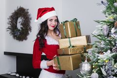 Beautiful girl with gifts in gold paper puts under the tree. Preparation for Christmas and new year. Celebration of winter royalty free stock images