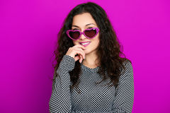 Beautiful girl glamour portrait on magenta in heart shape sunglasses, long curly hair Stock Images
