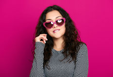 Beautiful girl glamour portrait on pink in heart shape sunglasses, long curly hair Stock Image
