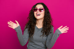 Beautiful girl glamour portrait on pink in heart shape sunglasses, long curly hair Royalty Free Stock Photos