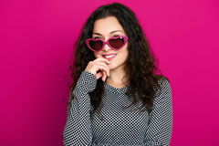 Beautiful girl glamour portrait on pink in heart shape sunglasses, long curly hair Stock Photography