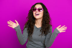 Beautiful girl glamour portrait on purple in heart shape sunglasses, long curly hair Royalty Free Stock Photo