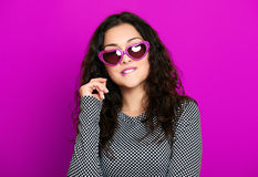 Beautiful girl glamour portrait on purple in heart shape sunglasses, long curly hair Royalty Free Stock Photos