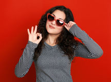 Beautiful girl glamour portrait on red in heart shape sunglasses, long curly hair royalty free stock photos