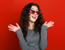 Beautiful girl glamour portrait on red in heart shape sunglasses, long curly hair Stock Photography