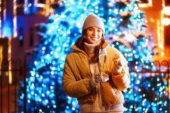 Beautiful girl with a glass of champagne and sparkle in the open air on the background of christmas tree in a winter. Beautiful girl or woman with a glass of royalty free stock photo
