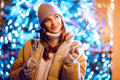 Beautiful girl with a glass of champagne and sparkle in the open air on the background of christmas tree in a winter. Beautiful girl or woman with a glass of stock photo