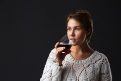 Beautiful girl with a glass of red wine on a black background. stock photo